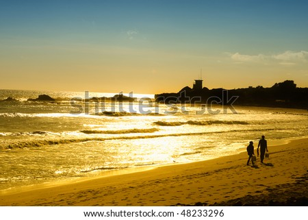 Sunset on the Pacific Ocean while a couple walk on the Malibu beach in California - stock photo