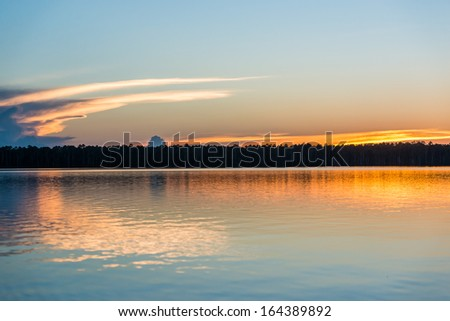 sunset on the river in the peruvian Amazon jungle at Madre de Dios Peru - stock photo