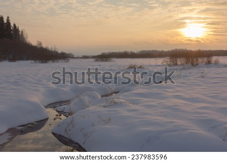Sunset on the river in the winter in frosty weather with fog