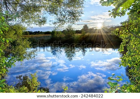 Sunset on the river with low clouds reflecting in the water - stock photo