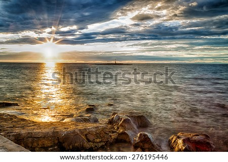 sunset on the rocks of the Mediterranean sea with red lighthouse on a small island in the background in Porec, Croatia in Europe - stock photo