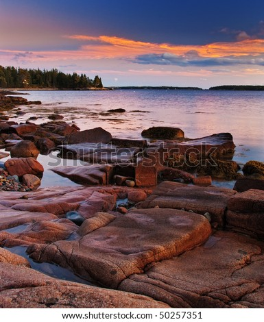 Sunset on the rocky Maine coast with a beautiful blue and orange sky.  The pink granite rocks are lit by the setting sun. - stock photo