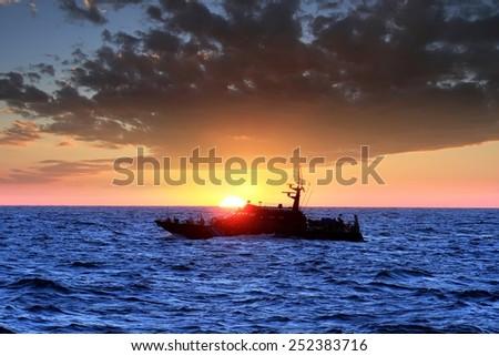 Sunset on the sea with a coastguard sailing - stock photo