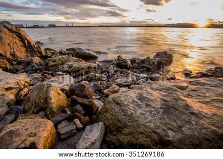 Sunset on the seashore with a lot of rock.