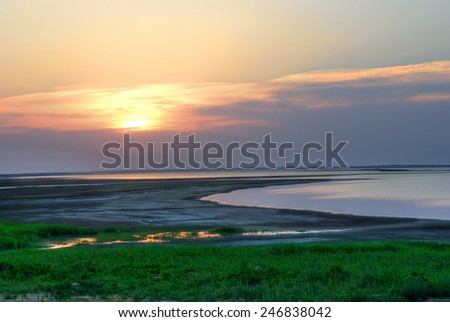 Sunset on the shore of the estuary. Summer landscape - stock photo