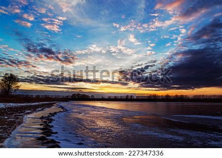 sunset on winter lake. - stock photo
