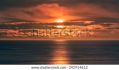 Sunset or Sunrise over Ocean - Orange Sun Setting or Sun Rising on Water with Beautiful Clouds in Pretty Sky - stock photo