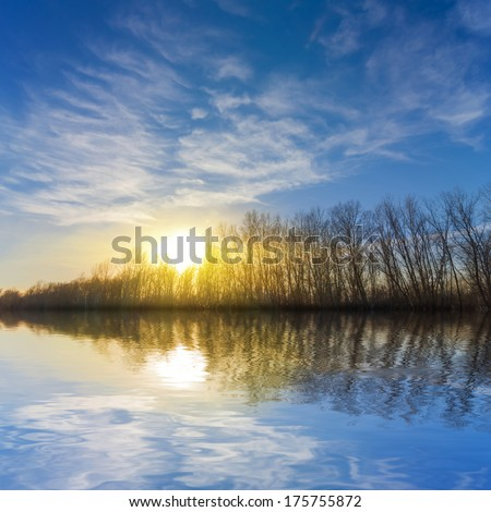 sunset over a calm lake - stock photo
