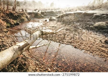 sunset over a creek running through an frosty autumnal landscape - stock photo