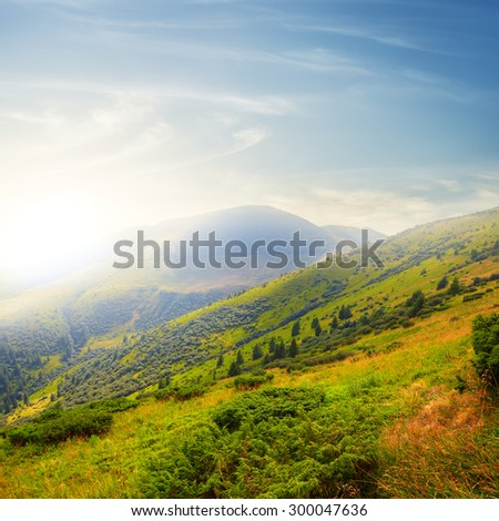 sunset over a green mountain valley - stock photo