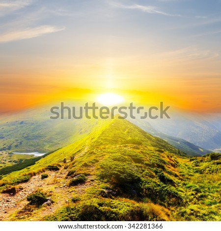 sunset over a green mountains - stock photo