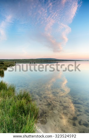 Sunset over a lake on Bodmin Moor in Cornwall - stock photo