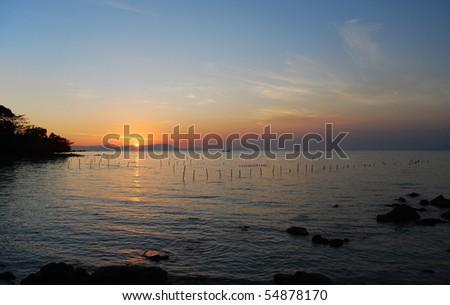 Sunset over a rocky coastline at Rabbit Island, Cambodia - stock photo