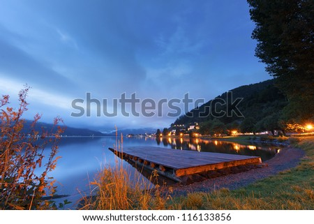Sunset over a tranquil lake with a wooden jetty and colourful lights lining the shore - stock photo
