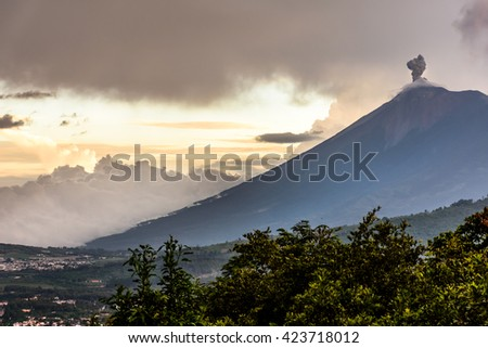 Sunset over active smoking Fuego volcano near Spanish colonial town & UNESCO World Heritage Site of Antigua, Guatemala, Central America - stock photo
