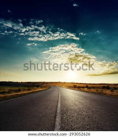 sunset over asphalt road with white line - stock photo