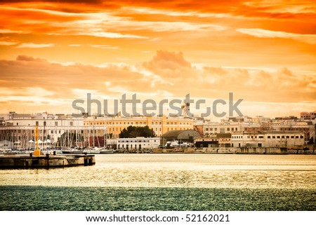 Sunset over Bari city in Italy seen from the harbour. - stock photo