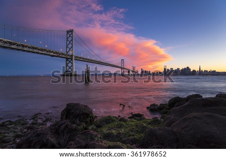 sunset over bay bridge / san francisco city view during a colorful sunset with clouds over the city skyline