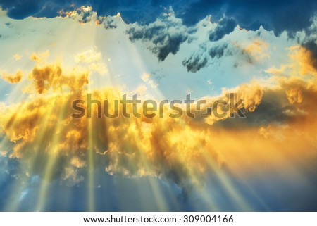 Sunset over beautiful blue sky with sun shining through clouds - stock photo