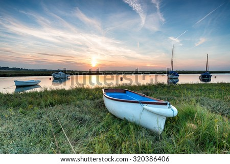 Sunset over boats on the salt marshes at Blakeney on the north coast of Norfolk - stock photo