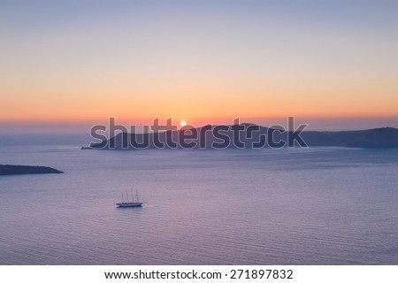 Sunset over Caldera volcano with a ship on the foreground. Santorini, Greece - stock photo