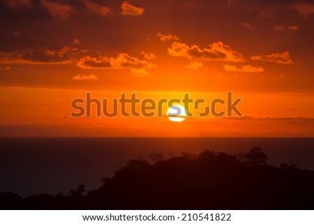 Sunset over Costa Rica. Sun reaching ocean through the clouds, Matapalo, Costa Rica 2013 - stock photo