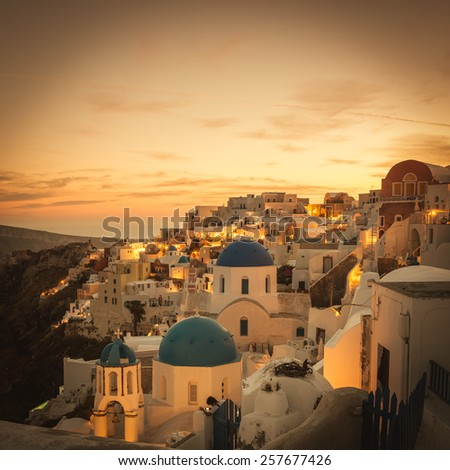sunset over famous blue and white city Oia,Santorini - stock photo