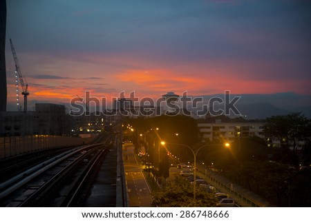 Sunset over Kuala Lumpur. Residential buildings, highrise construction sites with cranes and a water tower in centre. Elevated rail tracks and road below.  - stock photo