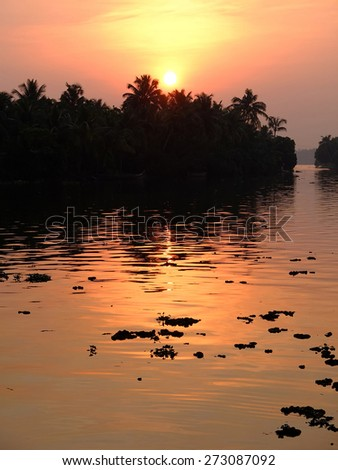 Sunset over lake in the backwaters of Kerala, India. - stock photo