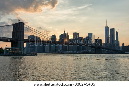 Sunset Over Manhattan Skyline with Brooklyn Bridge in Foreground with View of East River, New York City, New York, USA - stock photo