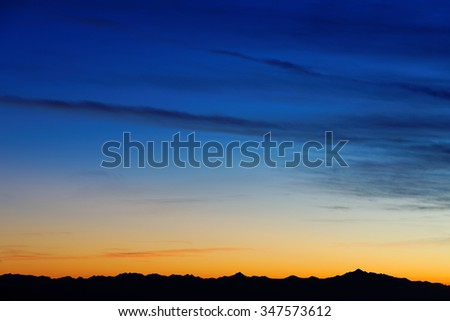 Sunset over mountain range on horizon with sky color gradient