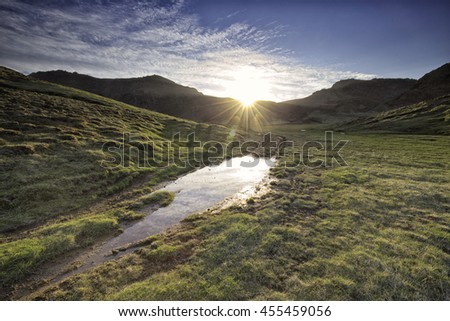 Sunset over mountains in southern Iceland, green fields bathed in golden sunlight before the last rays disappear. - stock photo
