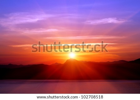 sunset over mountains near sea