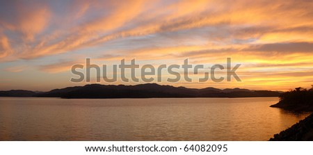 sunset over moutains and lake - stock photo