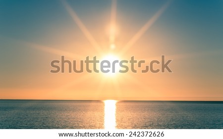 Sunset over Ocean - Bright Orange Sun Setting on Beautiful Blue Water - stock photo