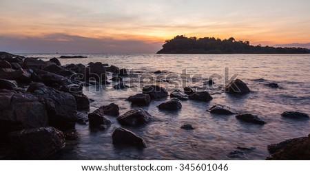 Sunset over rock sea beach - stock photo