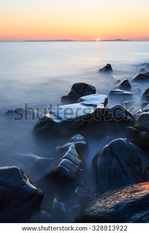 Sunset over rocky ocean in England.  - stock photo