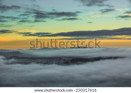 Sunset over San Francisco covered with fog - stock photo