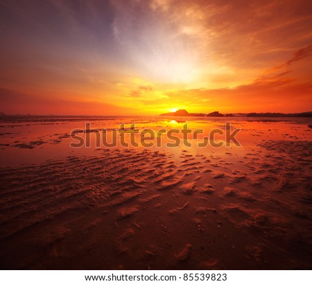 Sunset over sandy beach in low tide - stock photo