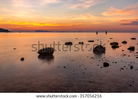 Sunset over sea and stones on a tropical island