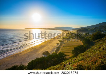 Sunset over Stinson Beach just north of San Francisco, California, USA.  Spring flowers in the foreground. - stock photo