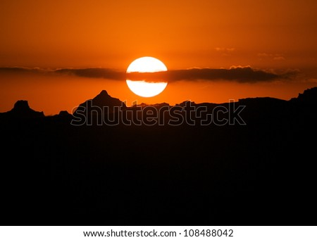 Sunset over the Badlands National Park, skyline silhouette - stock photo