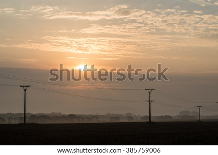 sunset over the fields in fog in summer with electricity poles - stock photo