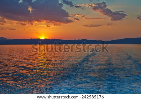 Sunset over the Greece, waves from the ferry, and the Mediterranean sea. The sun sets behind the mountains on the horizon. - stock photo