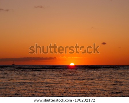 Sunset over the horizon of Pacific Ocean in Waikiki with boats in the water of Oahu, Hawaii. - stock photo