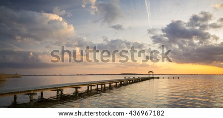 Sunset over the lake, a wooden bridge