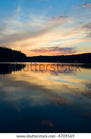 sunset over the lake and forest - stock photo