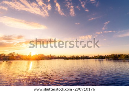 Sunset over the lake in the village. View from the coast, image in the orange-purple toning - stock photo
