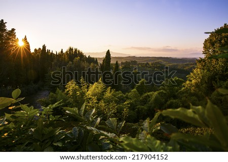 Sunset over the lush landscape in Tuscany  - stock photo