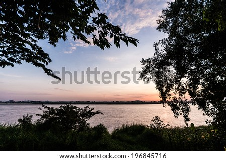 Sunset over the Mekong in Savanakhet in Laos. Here, the river marks the border with Thailand, on the other shore - stock photo
